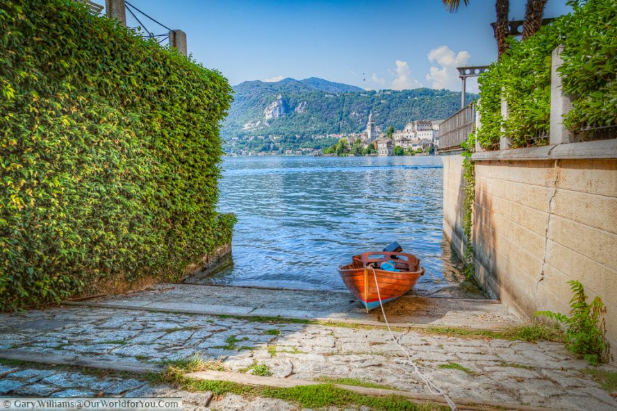 A boat moored up in Orta San Giulio , with Isola San Giulio in the background, Lake Orta, Italy