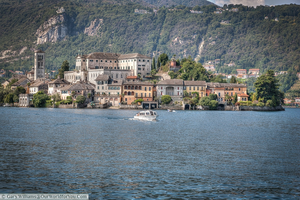 The Isola San Giulio, a boat returns to the jetty at Orta San Giulio, Lake Orta, Italy