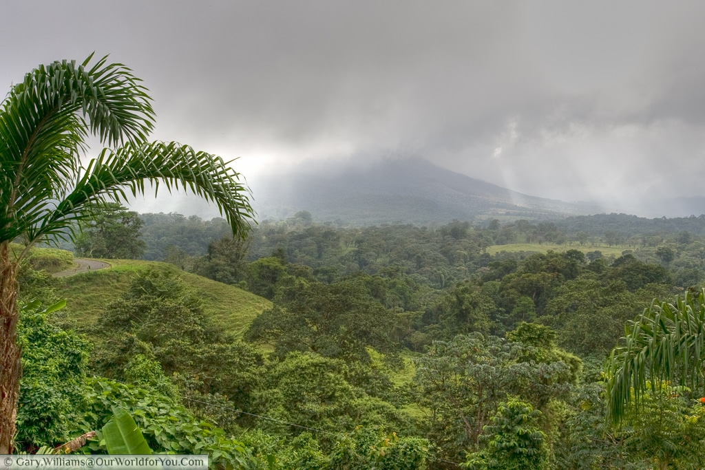 A view of the active Arenal volcano with the peak shrouded in cloud.