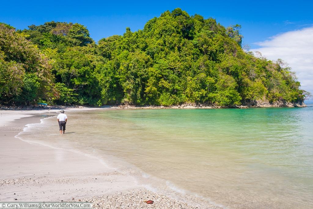 A lone individual walking along the Playa Biesanz at Manuel Antonio