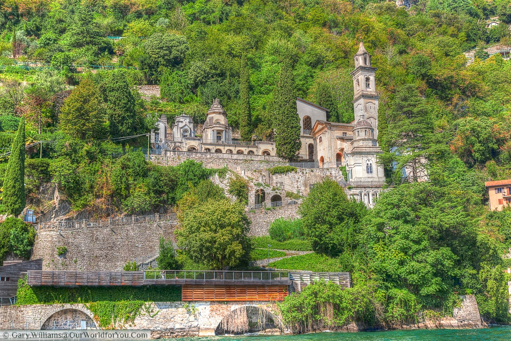 The Chiesa San Vittore nestles in the lush greens of the lakeside, Lake Como, Lombardy, Italy