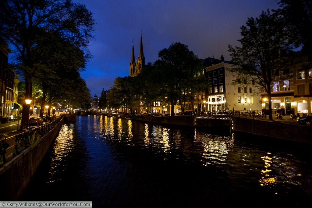 The Singel canal with the De Krijtberg Church piercing the skyline, Amsterdam, The Netherlands