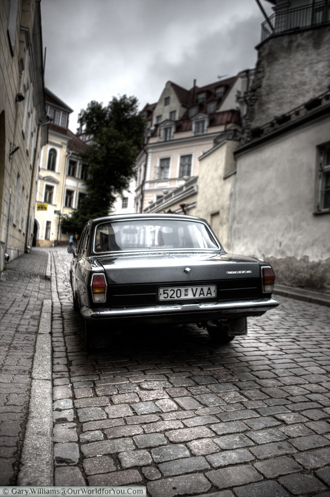 A picture of a Soviet era car parked up, set in a moody scene.