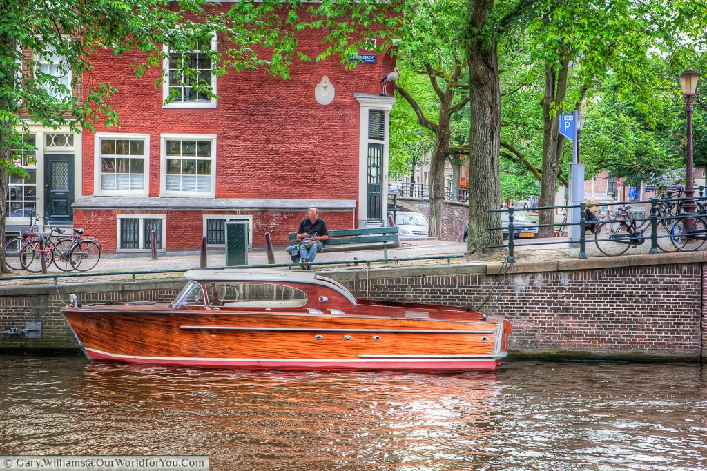 A wonderful wooden boat moored on the side of a canal in Amsterdam, The Netherlands