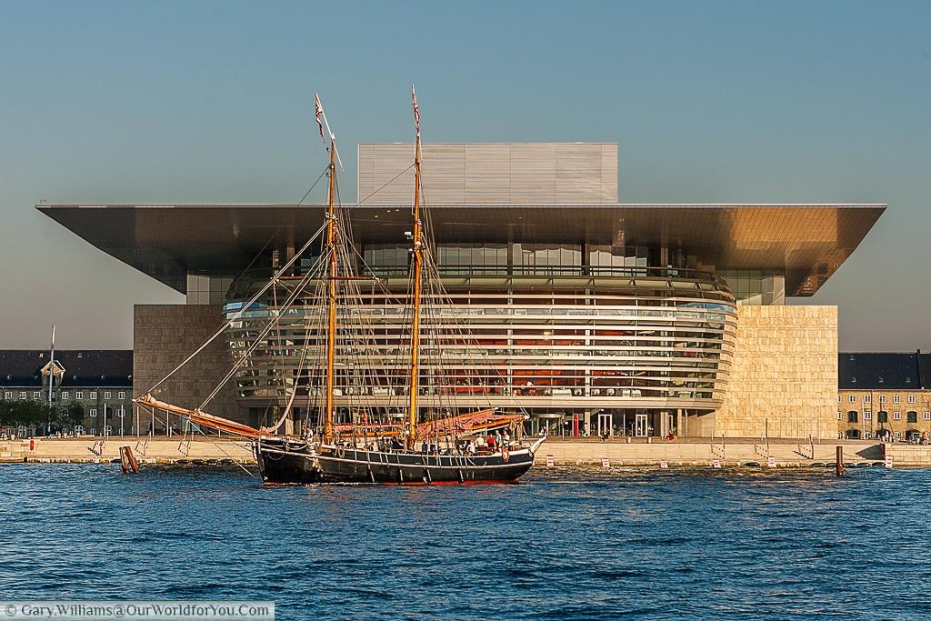 A sail boat floats in front of the Copenhagen Opera House, Copenhagen, Denmark