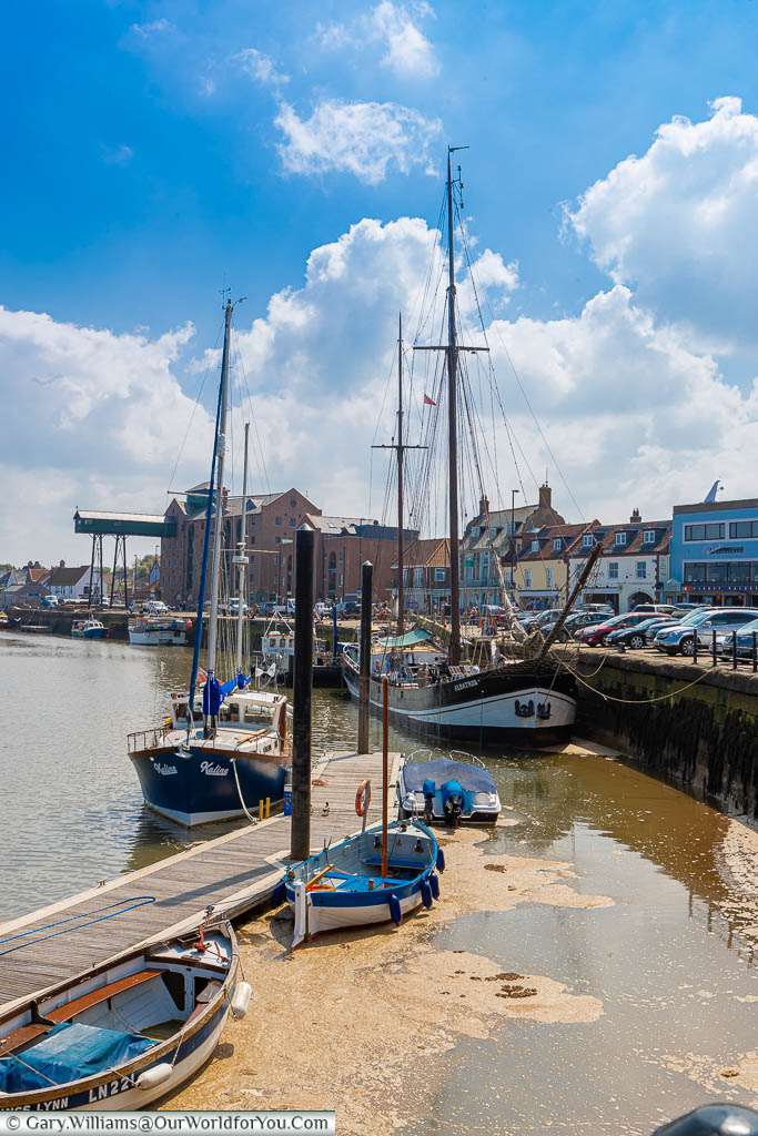 Tall sailing ships moored up on the quayside of Wells-next-the-Sea on the North Norfolk coastline