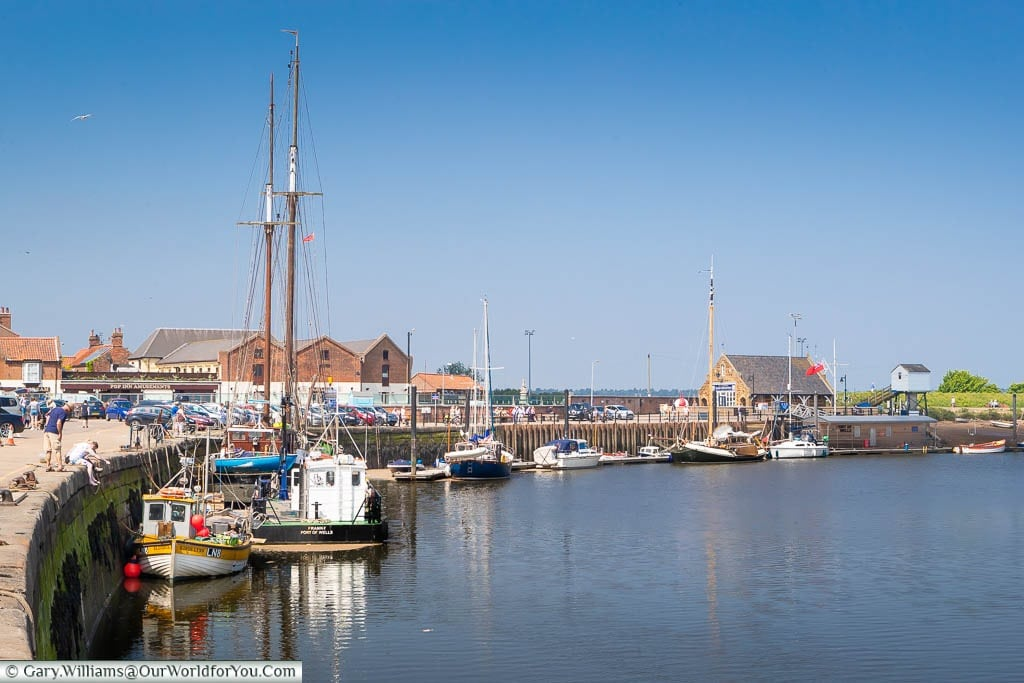 Boats moored up at the curved quayside at Wells-next-the-Sea on the North Norfolk coastline