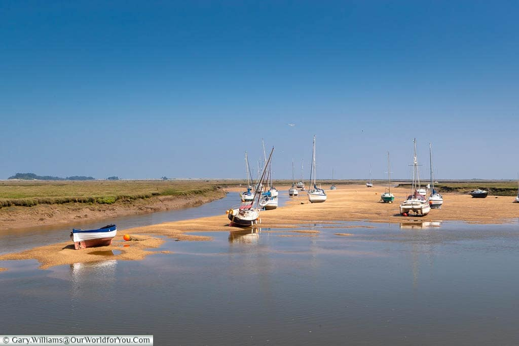 Small boats on the sand at Wells-next-the-Sea at low-tide under a beautiful blue sky in Norfolk
