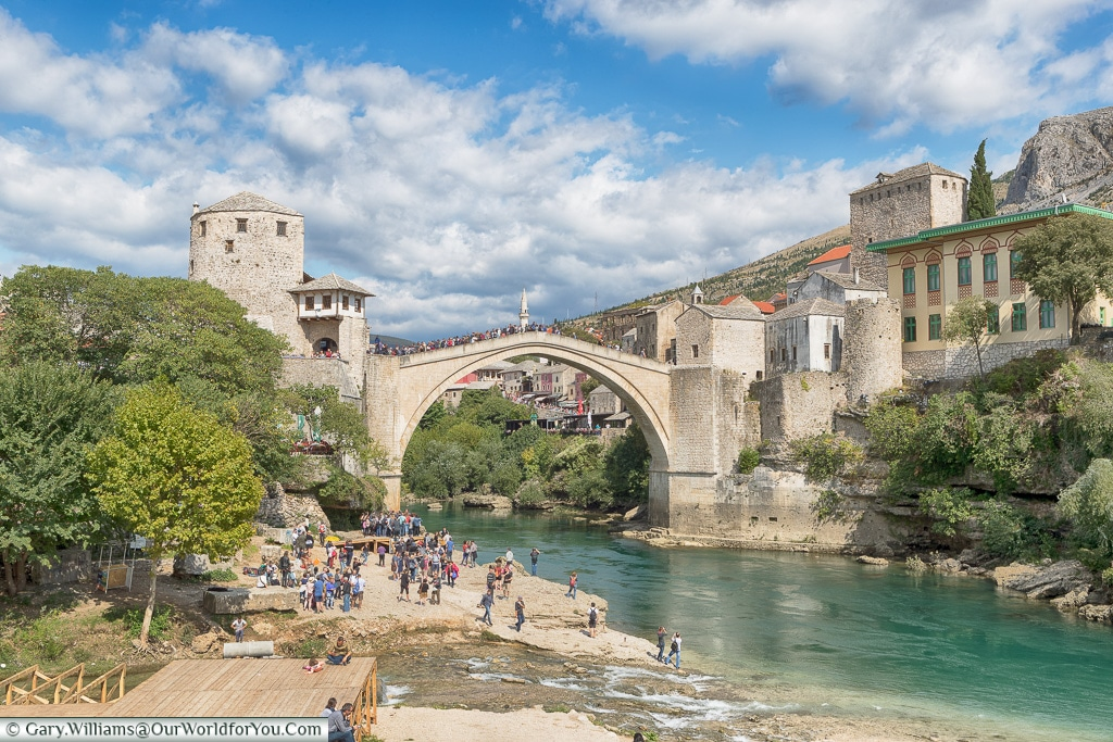 A stream joins the Neretva River, with the The Stari Most  in the background, Mostar, Bosnia and Herzegovina