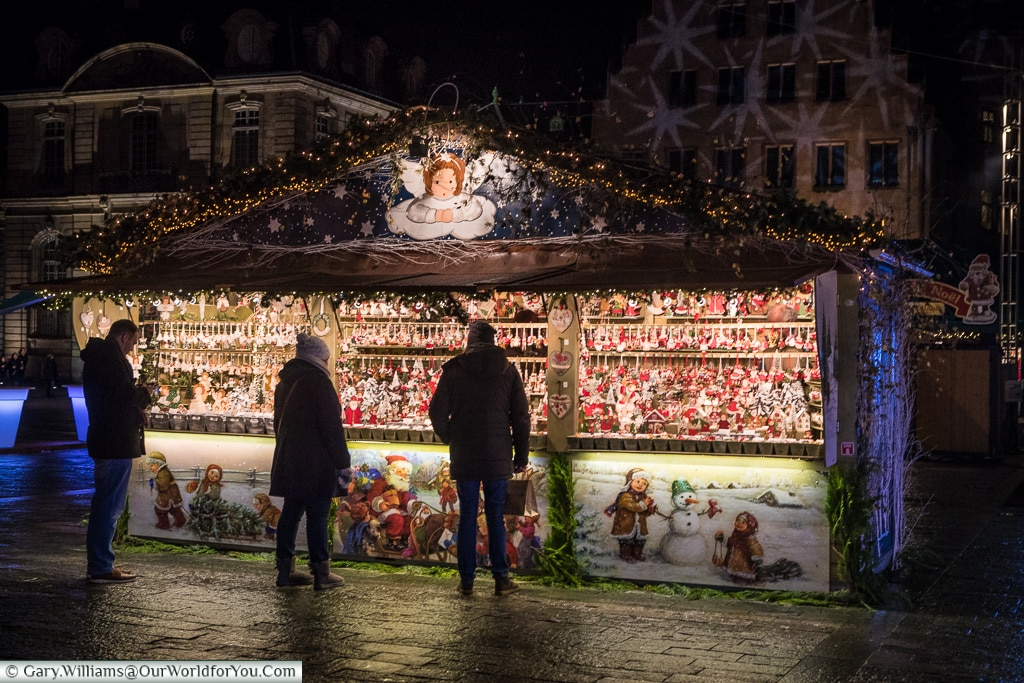 A Christmas market stall in the Place De La Cathédrale decorated with Christmas scenes of Santa and his sleigh, children with a snowman and an angel looking down at the shoppers perusing its extensive range of Christmas decorations.