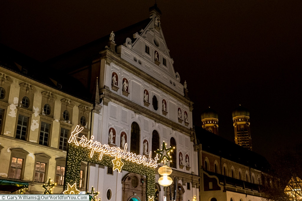A lit sign welcomes you to the Kripperlmarkt Christmas market, against the backdrop of the historic buildings that line the Neuhauser Straße with the towers of Munich Cathedral visible in the background.