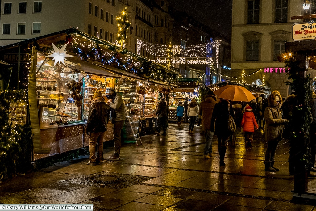 A collection of huts on the edge of one of Munich's markets as it drizzles and the pavement glistens.