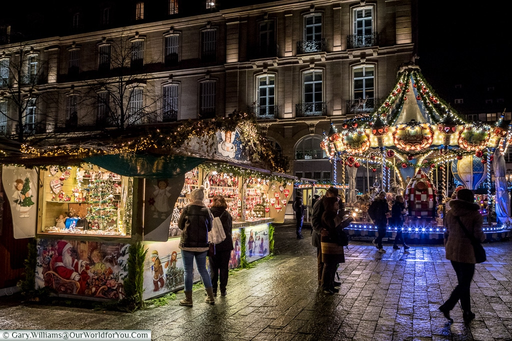A small group of people gather between a Christmas market stall and the carousel in Place De La Cathédrale.