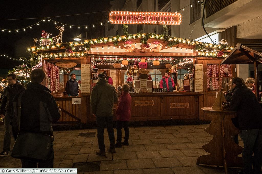 A brightly lit Glühwein hut in Frankfurt's quayside Christmas market at night.  People are coming and going, others are perched around wooden tables, shaped like Christmas trees enjoying their drinks.