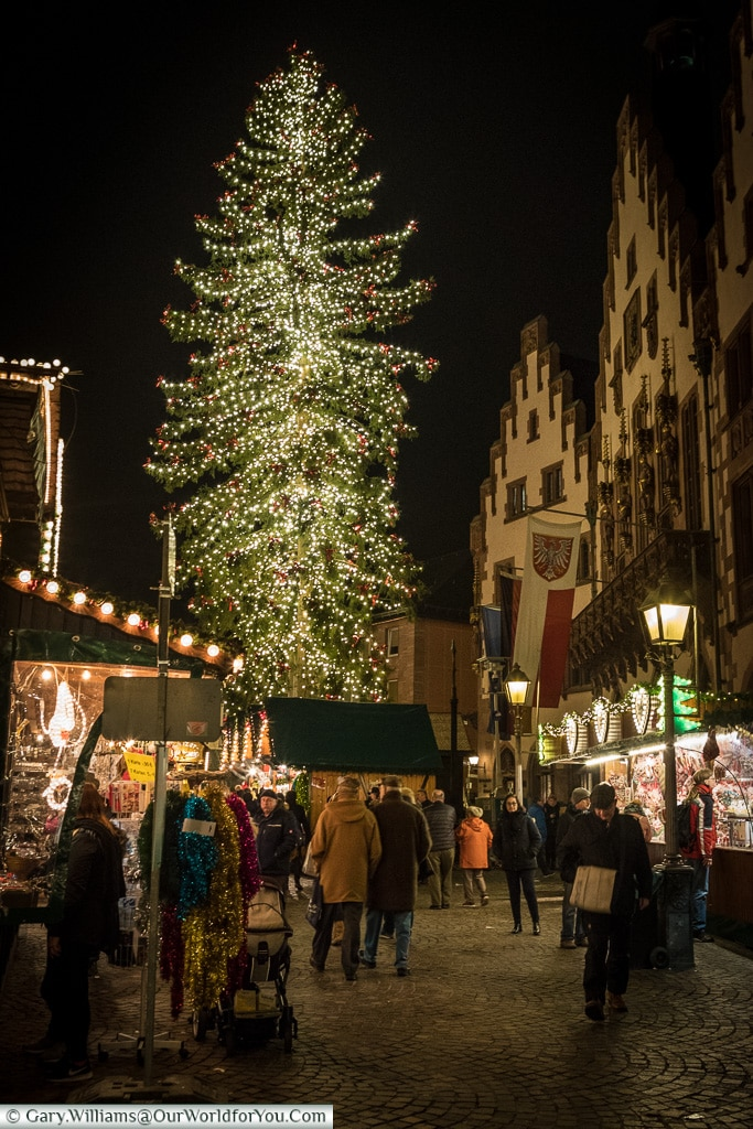 Looking down one of the rows, across the cobbles, of the Römerberg Christmas market at night to the vast, brightly lit, Christmas tee that dominates the view.