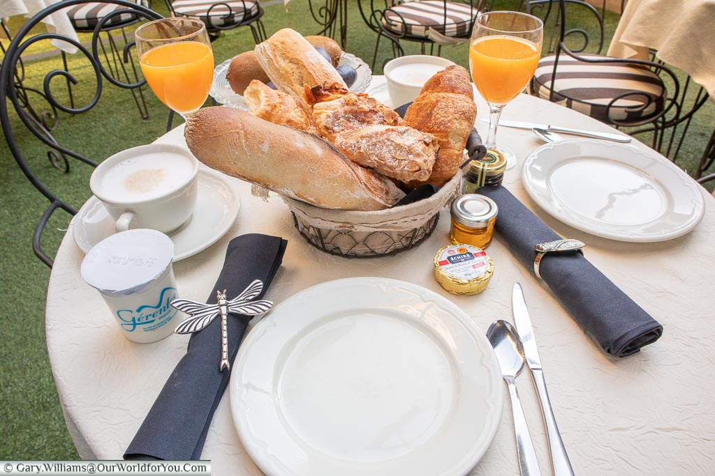 Breakfast at our table in Hotel Gounod.  A selection of breads and pastries with a fresh orange juice find a cup of coffee.
