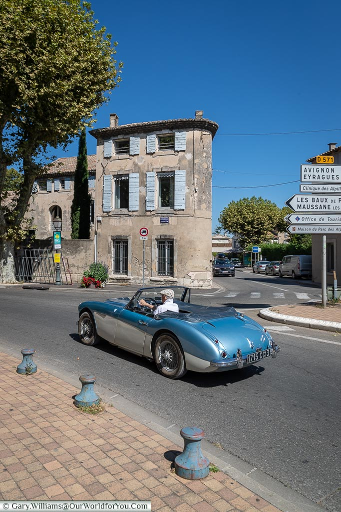 A classic 1960's Austin Healey convertible sports car in metallic blue & cream as it passes Saint-Rémy-de-Provence in front of a blue shuttered home on a beautiful sunny day.