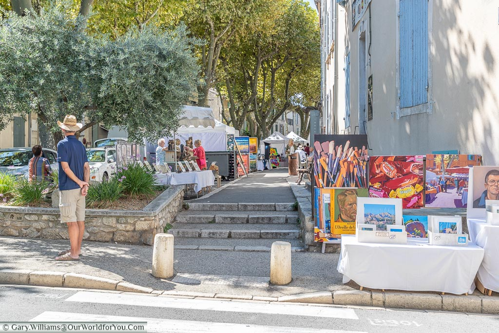 People perusing works of art at the town's quarterly market fare that lines the roads of Saint Remy de Provence.