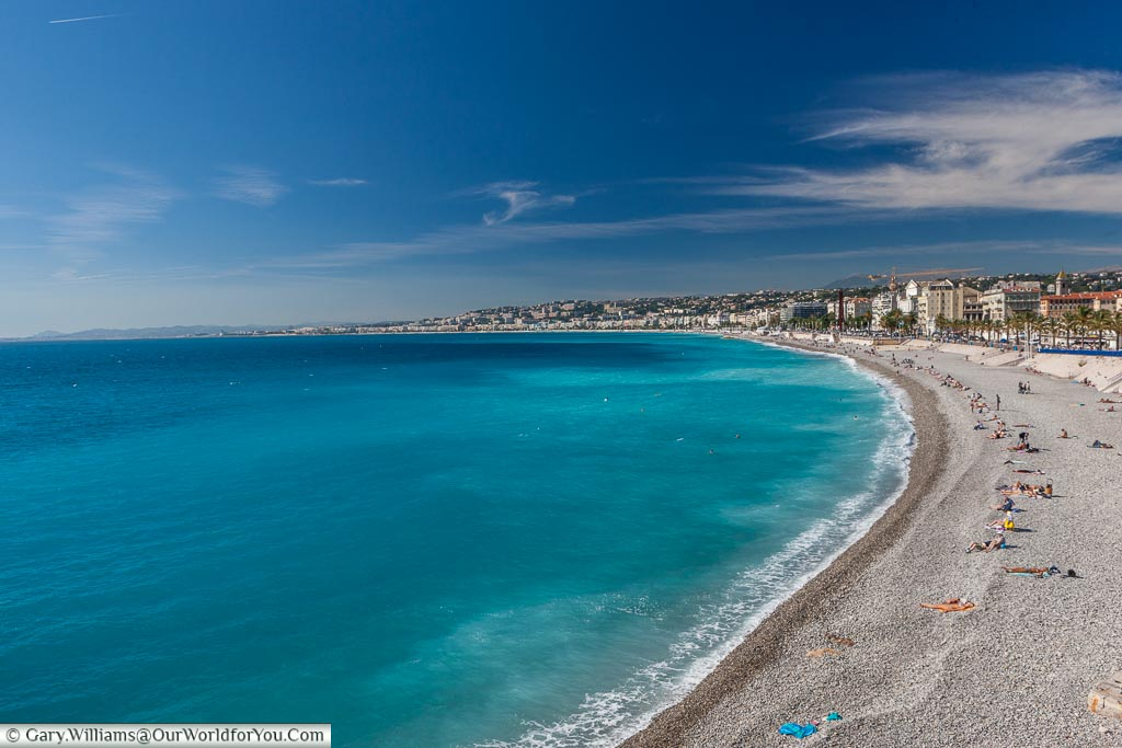 The beautiful azure blue waters of the Mediterranean, set against the grey stone beach of Nice