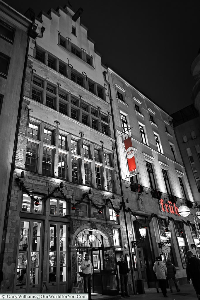 The front of the Früh am Dom brewhouse in black and white with the red of the Früh logo the only colour in the image.