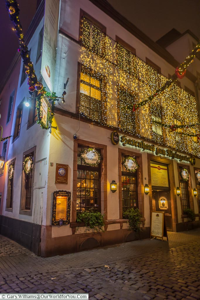 Brightly decorated pub of Haxenhaus at night on the cobbled lanes close to the River Rhine.