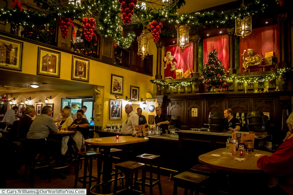 Inside the Christmas decorated Bierhaus en d'r Salzgass, a traditional Kolsch pub with beer barrels on the bar.