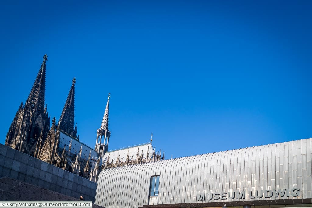 A shot of the silvery aluminium roof of Museum Ludwig with Cologne's cathedral in the background set against a deep blue sky.