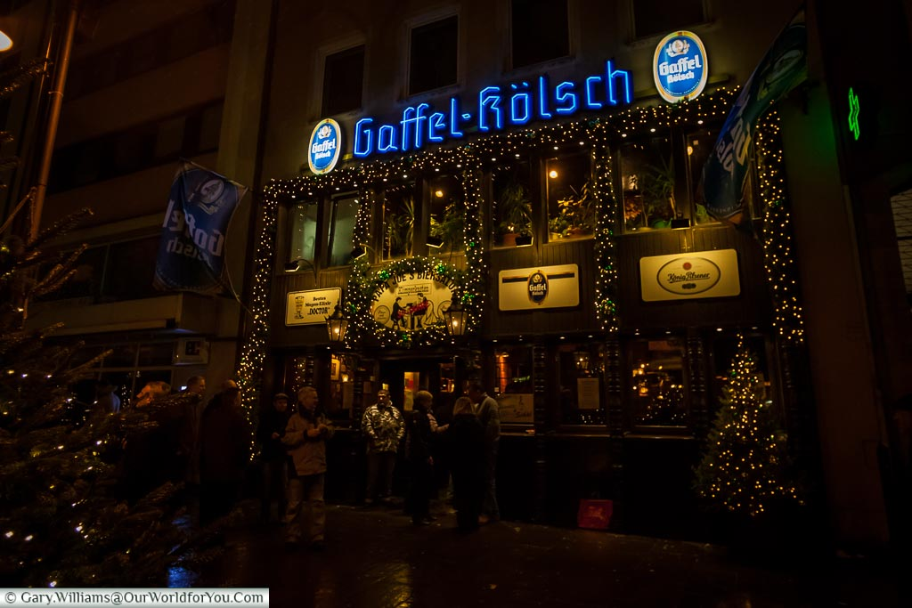Outside Papa Joe's Biersalon In the evening. The pub is decorated with twinkle lights and sign displaying they serve Gaffel Kölsch.