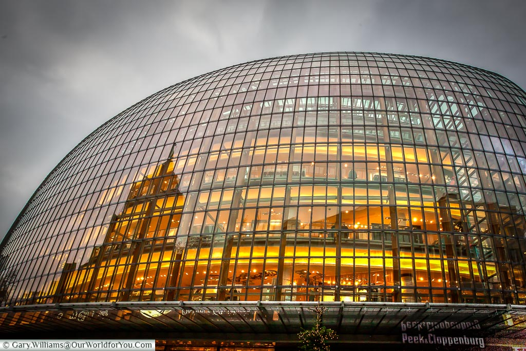 The old glass egg shaped Department store of Peek & Cloppenburg under dark grey winter sky. The scene is lit with a golden light coming from inside the store.  It's one of the main Department stores in Cologne.