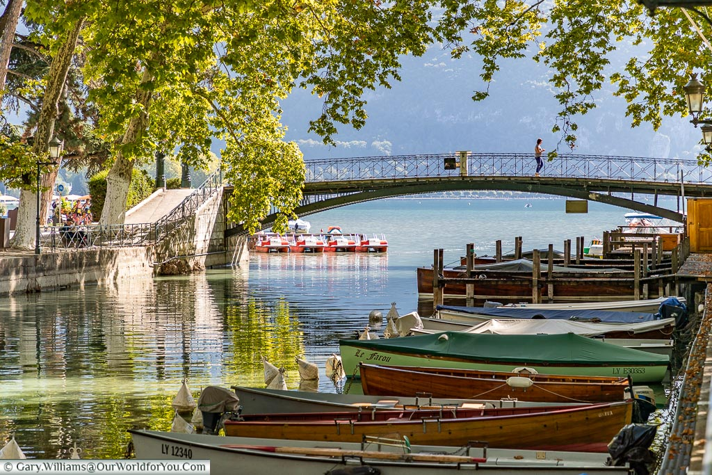 Wooden rowing boats moored up on the Canal de Vassé under dappled shade, in front of the Pont des Amours on the edge of Lake Annecy