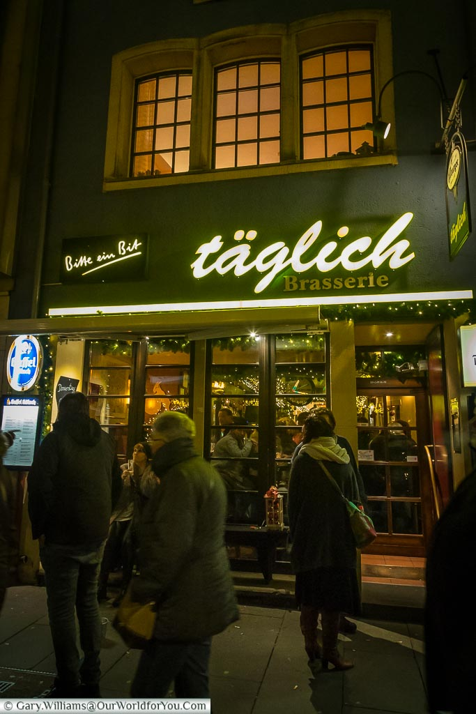 People strolling past the Täglich Brasserie.  The narrow front of the shop hides the depth of the building, and its long bar.