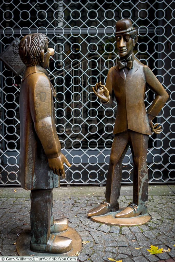 Two life-size brass statues of characters that represent the soul and character of the city of Cologne.