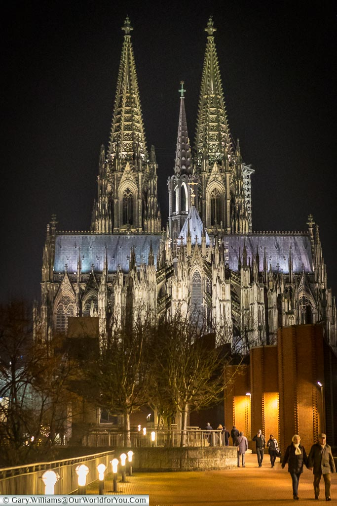 A view of Cologne cathedral in the evening from the east after just crossing the Hohenzollernbrücke bridge.  The cathedral is beautifully floodlit and looks stunning against the dark sky.
