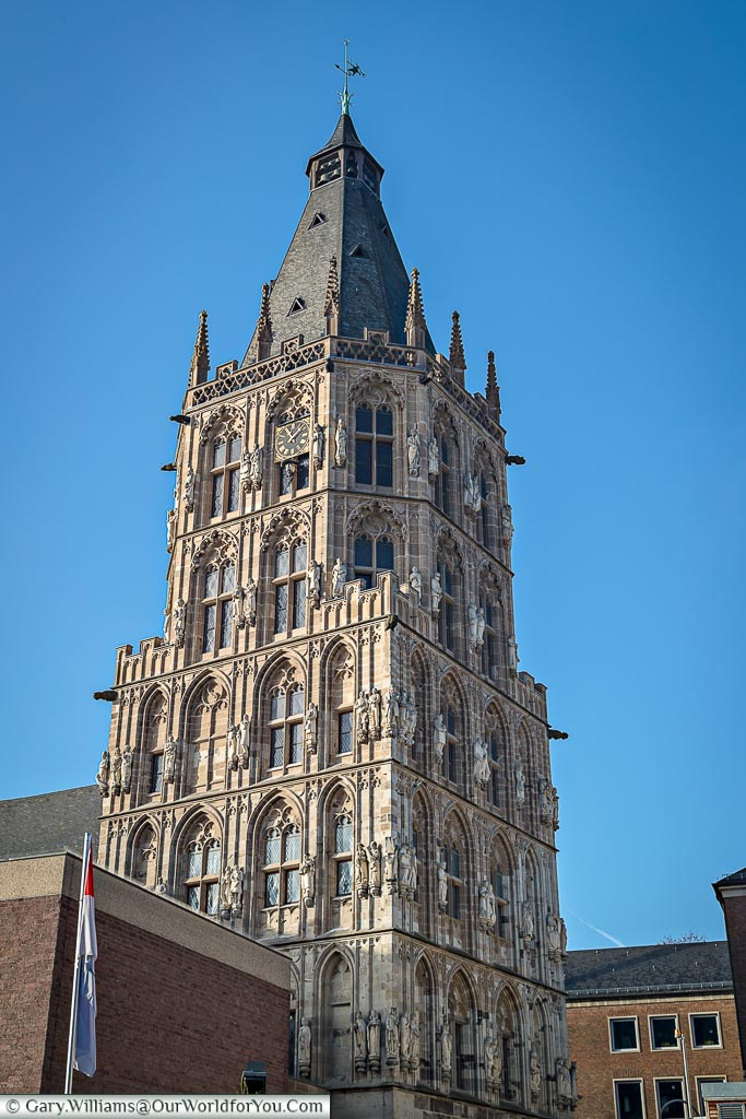 A portrait shot of the detailed gothic tower of Cologne's Rathaus against a deep blue sky.