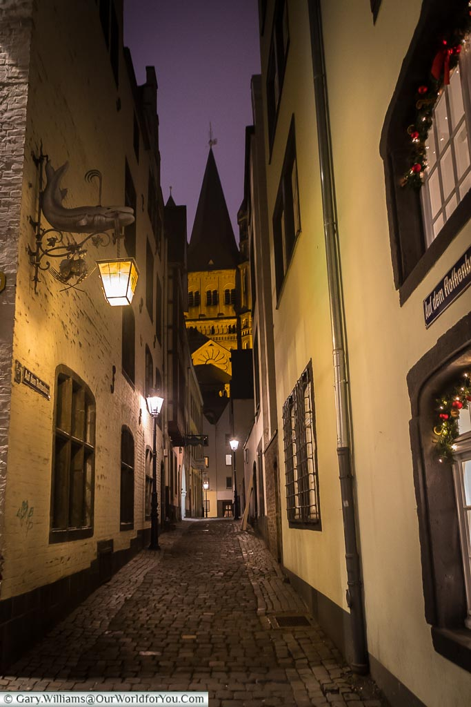 One of the quiet narrow cobbled lanes of the Old Town of Cologne at dusk, lit by lanterns hanging from ornate hooks. At the end of the line is the tower to one of Cologne's many churches