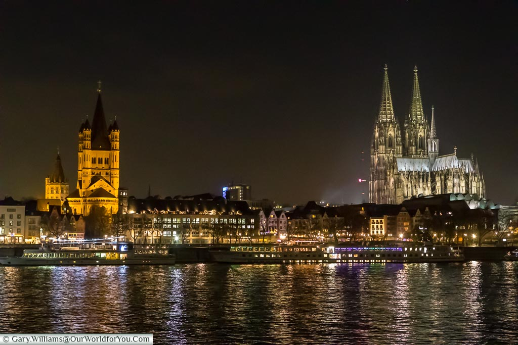 A view across the River Rhine at night with Cologne cathedral dominating the skyline on the right in Saint Martin's church dominating the skyline on the left. Pleasure craft line the edge of the riverbanks are waiting to take passengers on on an evening tour