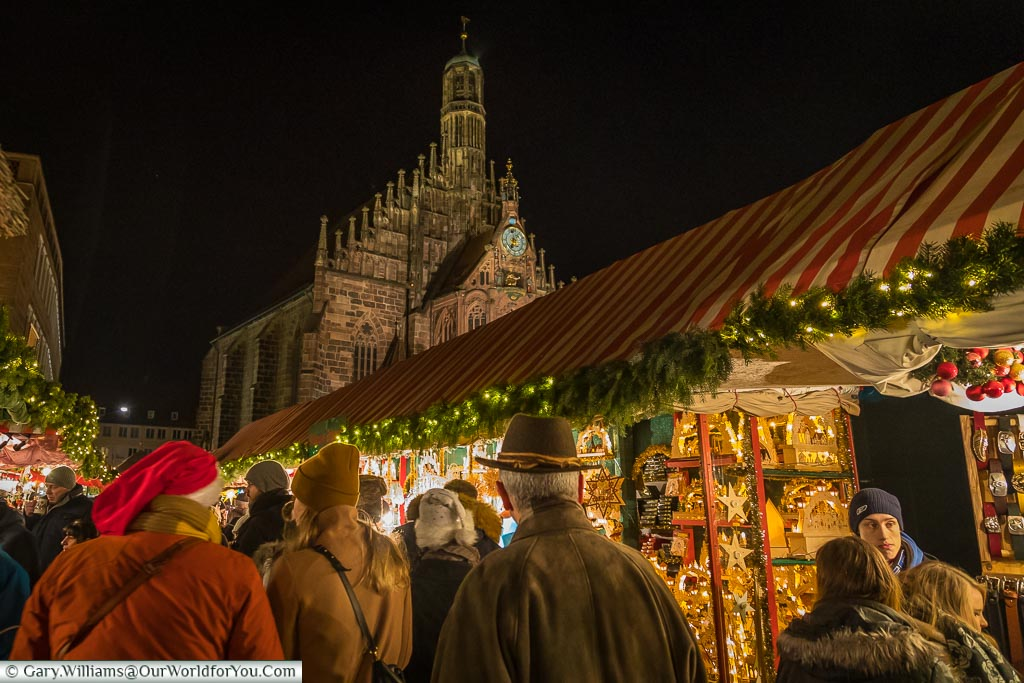 We are following the crowds through Nuremberg's main market, with the illuminated church in the background.