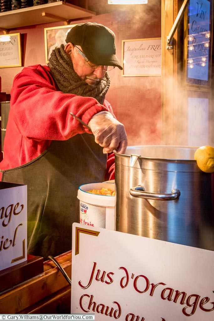 A mature man, wrapped heavily against the cold ladling out hot spiced orange juice at a stall in the Christmas markets.