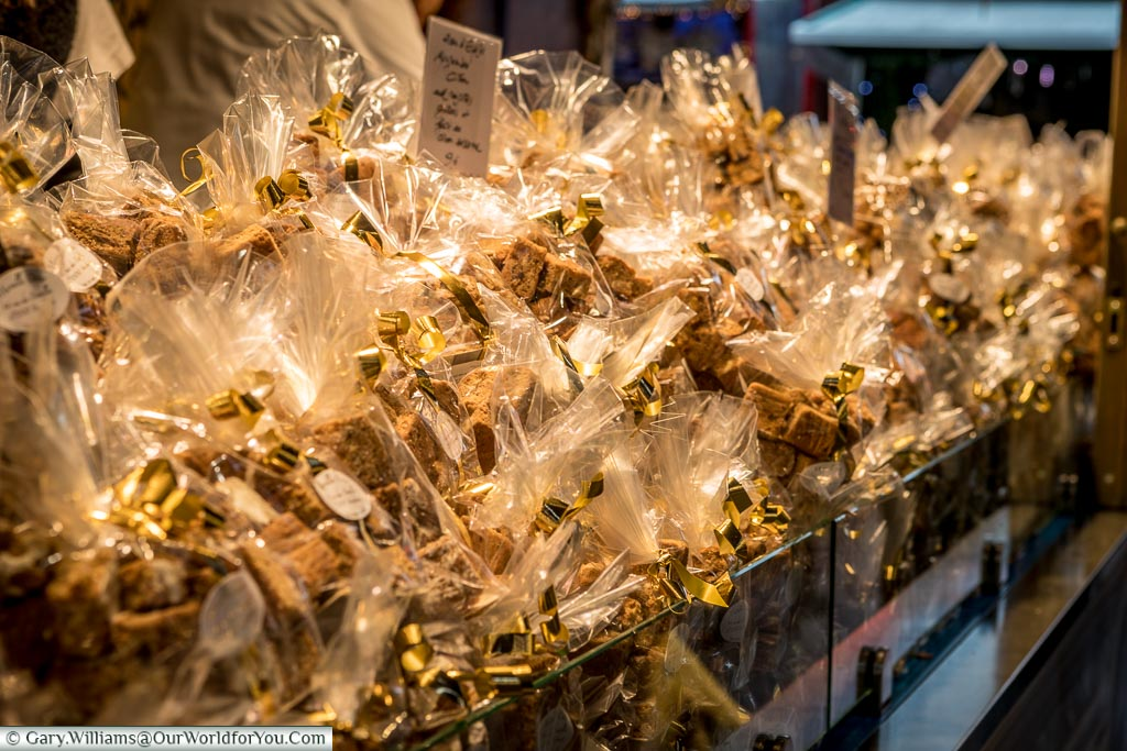A closeup of gingerbread in small cellophane packets, tied with gold ribbons on a Christmas market stall.