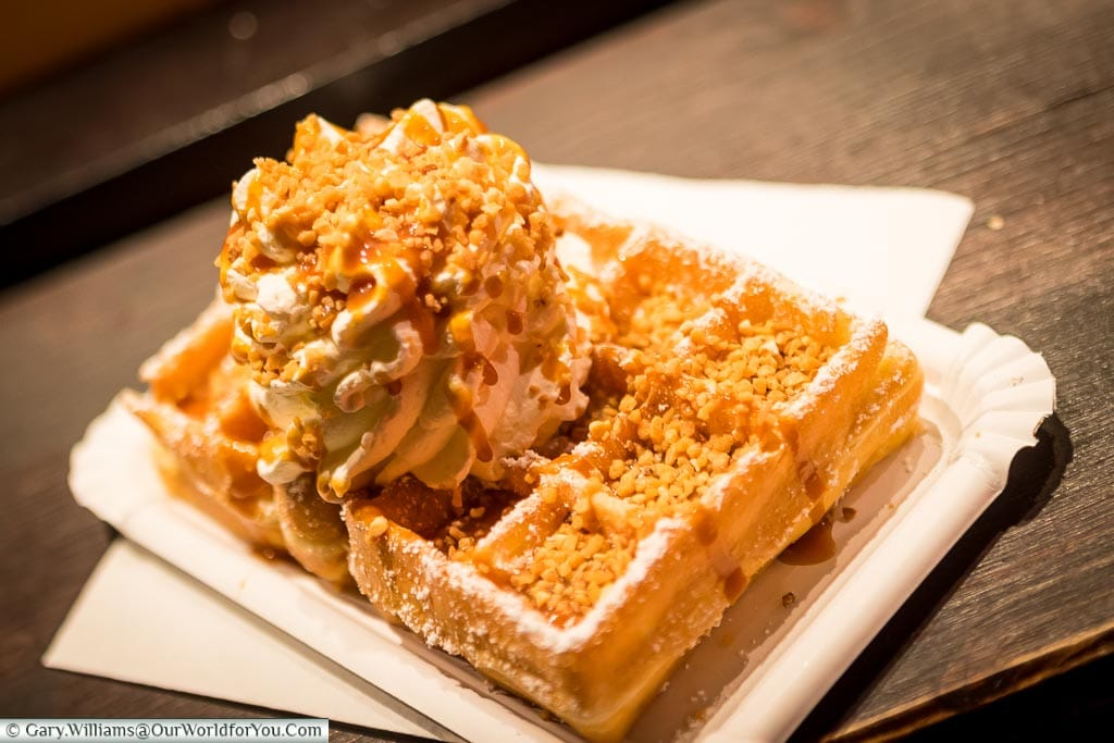 A crisp freshly cooked waffle topped with cream, caramel sauce and crunchy nuts all dusted with icing sugar in a paper plate on a German Christmas Market