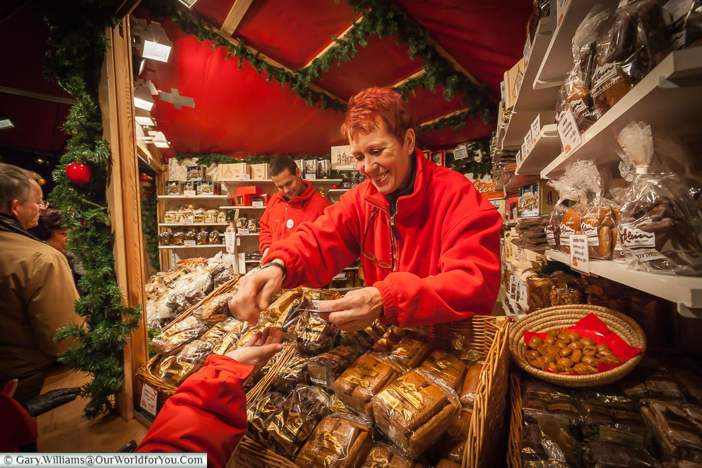 The Aachener Printen gingerbread stall in Cologne.  It's stacked his with all the different styles of gingerbread biscuits.  The lady behind the counter is handing Janis back her change after we've bought another bag load.