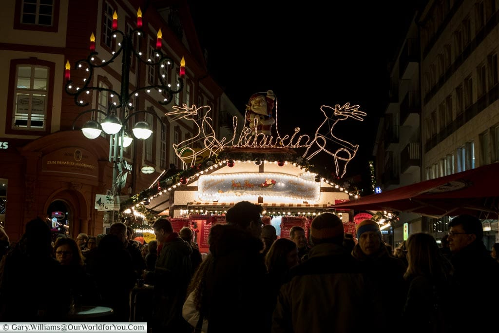A group of people gathered around a glühwein stall on the Christmas market at night.  The streel lamp has an additional advent candlelight attached, and the top of the booth has two illuminated reindeer either side of Santa and a glühwein sign.