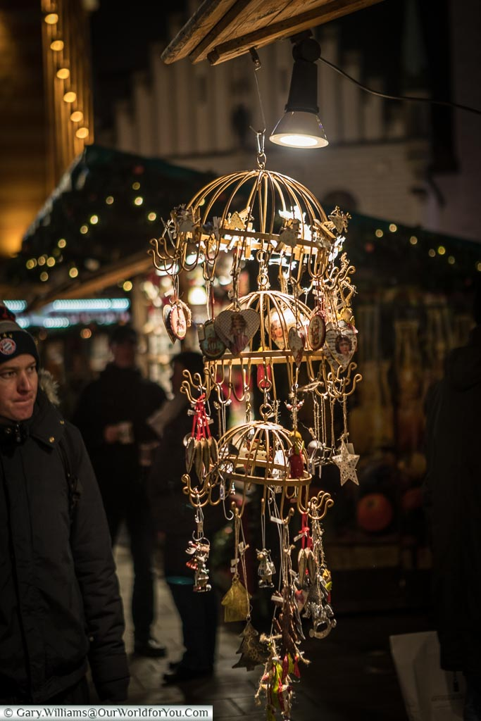 A hanger from a stall in Munich's Christmas market lit with a spotlight catch the decorations hanging from it.