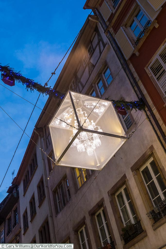 A beautiful chandelier, encased in a translucent cube suspended between two sides of the street, acting as a regular street light.