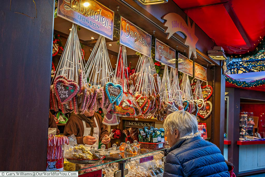 A woman inspecting the gingerbread at a Christmas market stall in Cologne. The display is full of hanging iced gingerbread hearts.