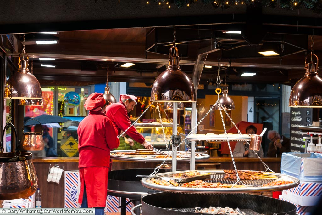 A selection of meats & sausages being cooked over charcoal in a German Christmas Market