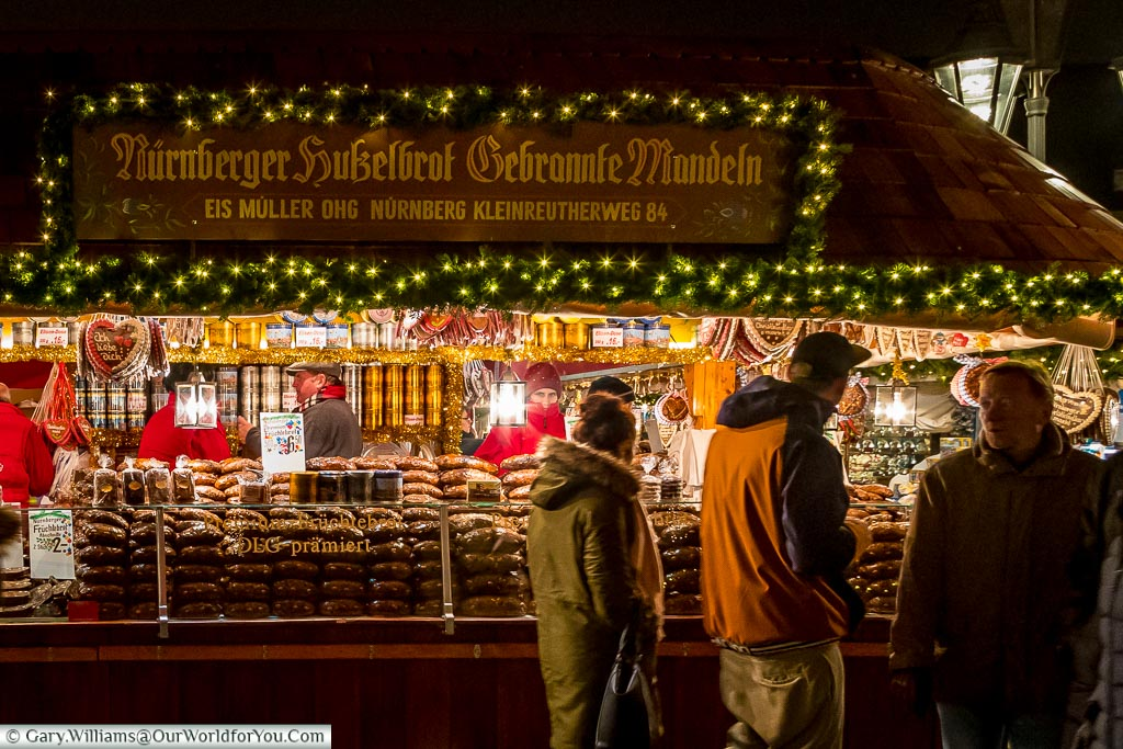 A stall stacked high with the Nuremberg gingerbread loaves as folks pass by.