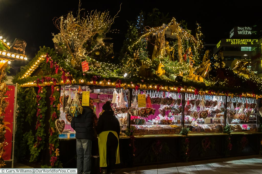 A festive nativity display glistening above a gingerbread stall in Stuttgart's Christmas Market