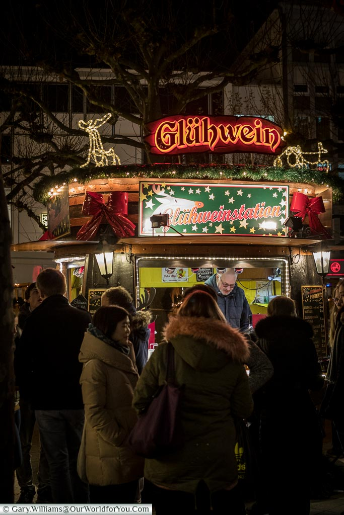 A group of people queuing at a Glühwein hut at the Hauptwach Christmas Market.