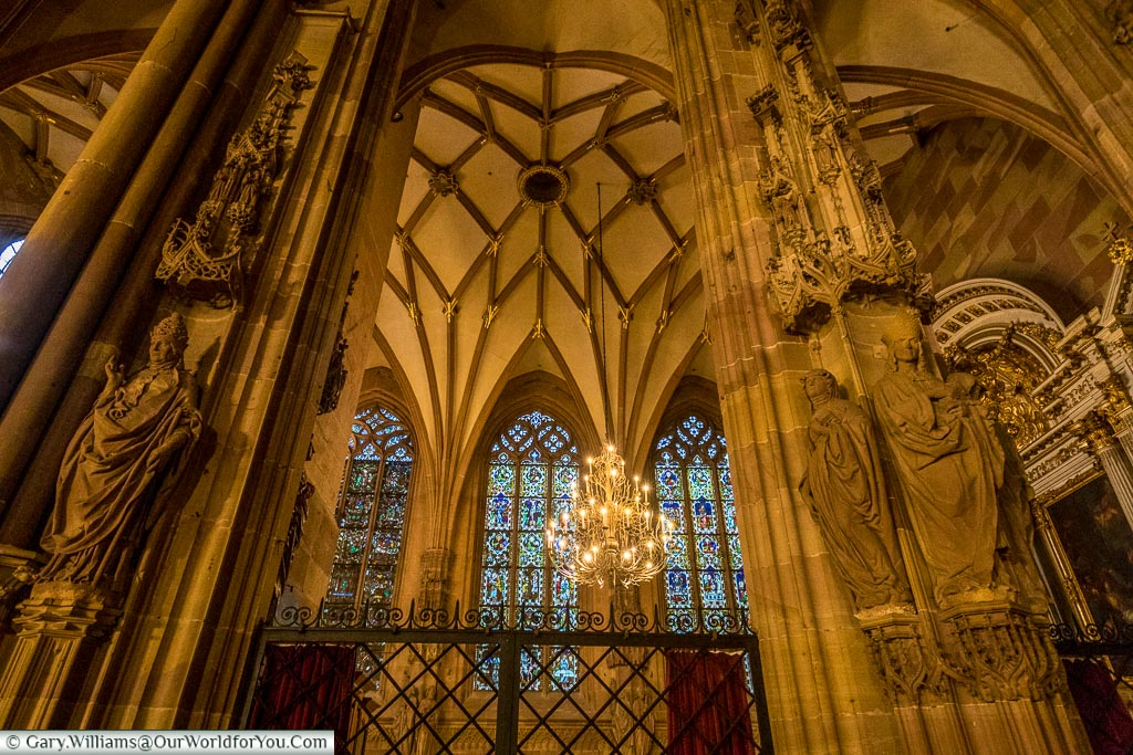 Inside the gothic Cathedral of Strasbourg looking through two pillars decorated with statues of the Virgin Mary and bishops towards a vaulted roof, from which an ornate chandelier is suspended in front of stained glass windows.